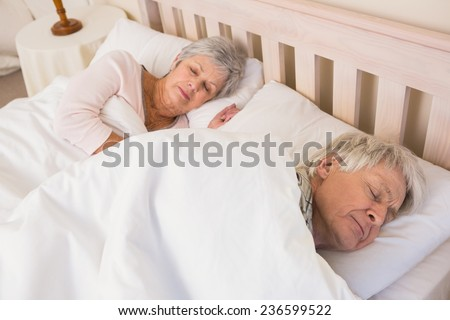 Senior couple sleeping in bed at home in the bedroom - stock photo