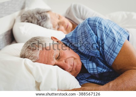 Senior couple sleeping on bed in bedroom - stock photo