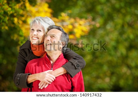 Senior couple smiling and looking at something in the park - stock photo
