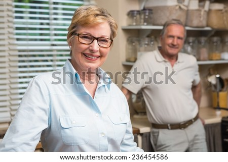 Senior couple smiling at the camera together at home in the kitchen - stock photo
