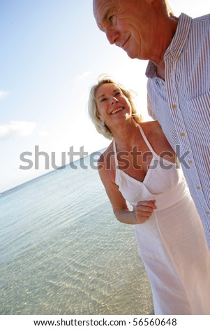 Senior couple smiling having a walk at the seaside - stock photo