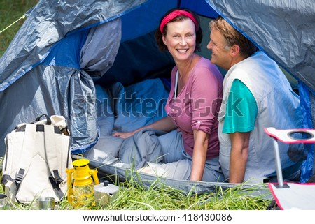 senior couple smiling inside their tent in a forest