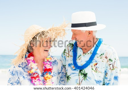 Senior couple standing at the beach on a sunny day - stock photo