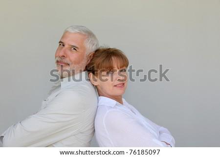 Senior couple standing back to back - stock photo