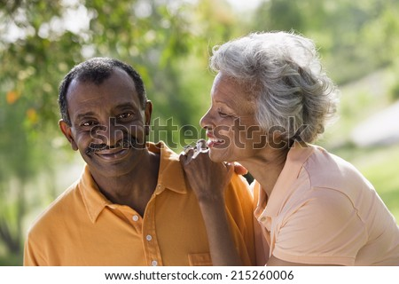 Senior couple standing in park, woman gazing affectionately at husband, smiling, close-up (tilt) - stock photo