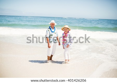 Senior couple standing in the water of the sea on a sunny day - stock photo