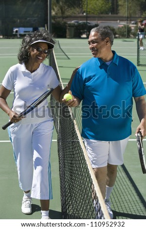 Senior couple standing next to each other on tennis court - stock photo