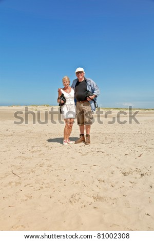 Senior couple standing on empty beach under clear blue sky on hot summer day.