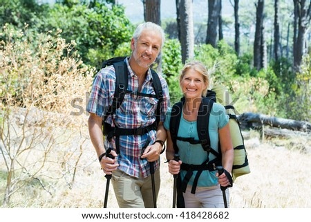 Senior couple standing with their stick in a forest - stock photo