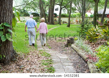 Senior couple strolling down a garden path together.  A metaphor for life's journey. - stock photo
