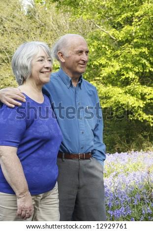 Senior couple take a walk in woodland full of beautiful springtime bluebells. - stock photo