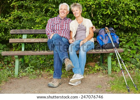 Senior couple taking break on bench while hiking in nature - stock photo