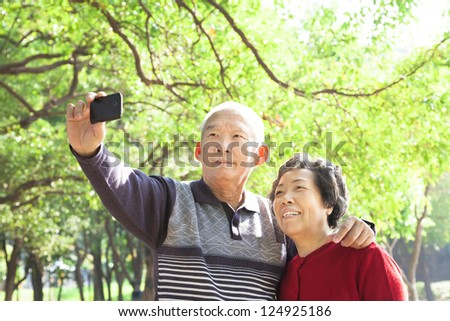 Senior couple taking picture of themselves outdoor - stock photo
