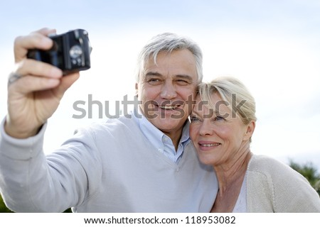 Senior couple taking picture of themselves outside - stock photo