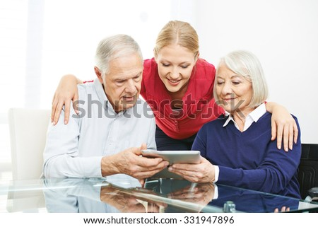 Senior couple testing apps on tablet computer with their granddaughter - stock photo