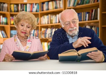 Senior couple together reading at the library. - stock photo