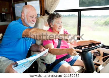 Senior couple traveling in their motor home.  The husband is giving directions to the wife. - stock photo