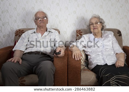 Senior couple using a remote to change channel - stock photo