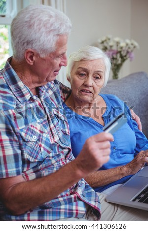 Senior couple using credit card and laptop at home - stock photo