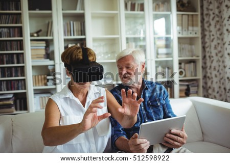 Senior couple using digital tablet and virtual reality headset in living room
