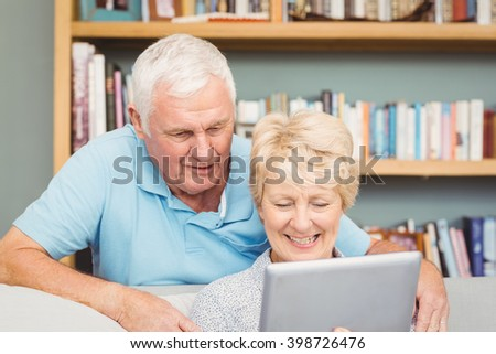 Senior couple using digital tablet at home - stock photo