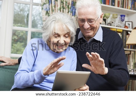 Senior Couple Using Digital Tablet For Video Call With Family - stock photo