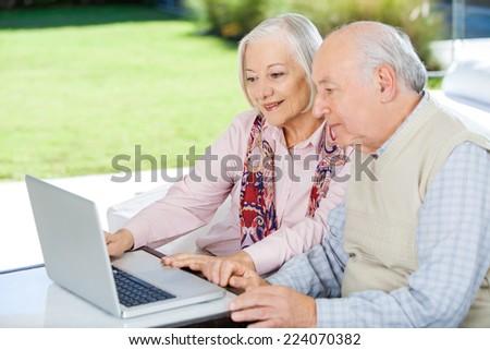 Senior couple using laptop while sitting at nursing home porch - stock photo