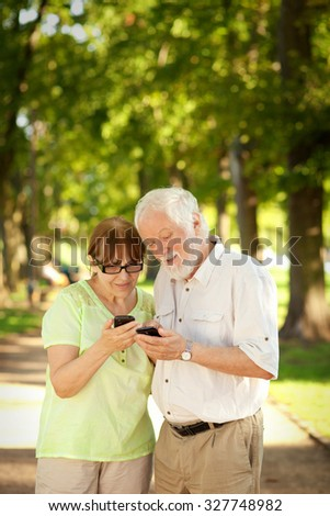 Senior couple using smart phones outdoors, shallow depth of field