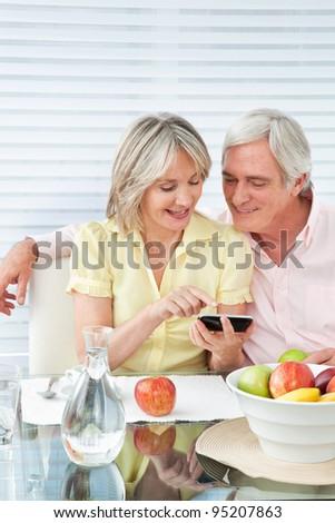 Senior couple using smartphone at breakfast table - stock photo