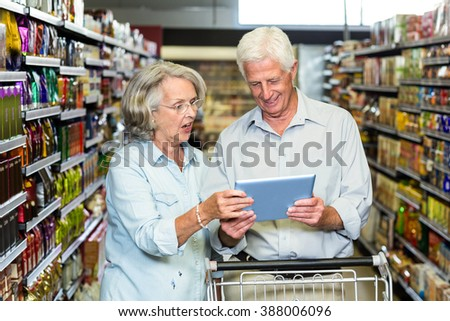 Senior couple using tablet at the supermarket with cart