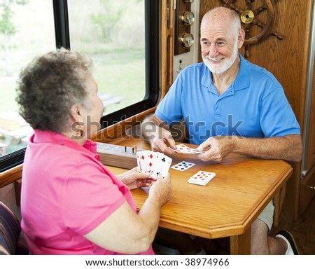 Senior couple vacationing in their motor home, playing a game of cribbage. - stock photo