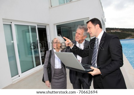 Senior couple visiting luxury villa with real-estate agent - stock photo