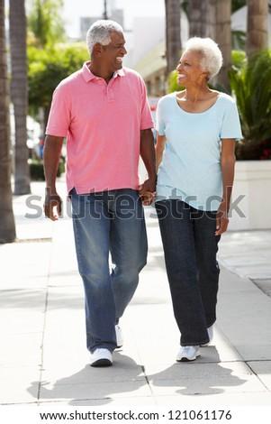 Senior Couple Walking Along Street Together - stock photo