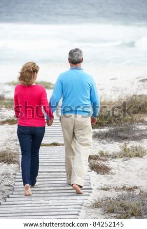 Senior couple walking by the sea - stock photo