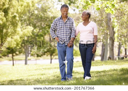 Senior  couple walking in park - stock photo