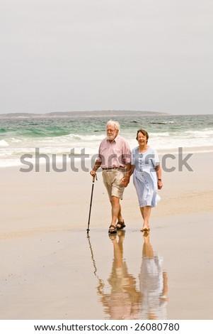 Senior couple walking on beach - stock photo