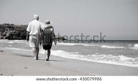 senior couple walking on the beach - stock photo