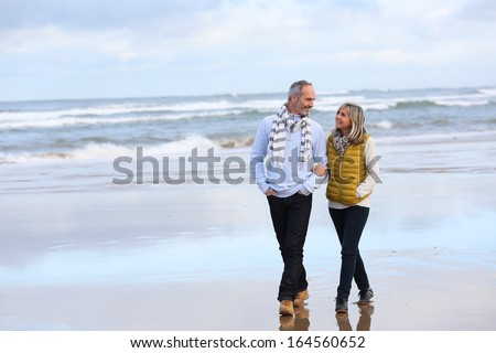 Senior couple walking on the beach in winter time - stock photo
