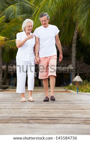 Senior Couple Walking On Wooden Jetty