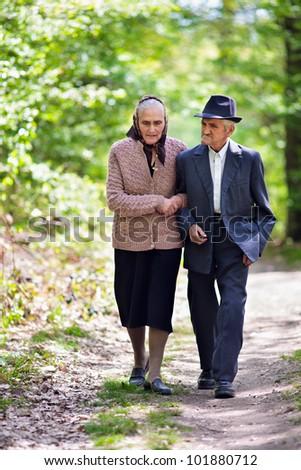 Senior couple walking outdoor in the park - stock photo