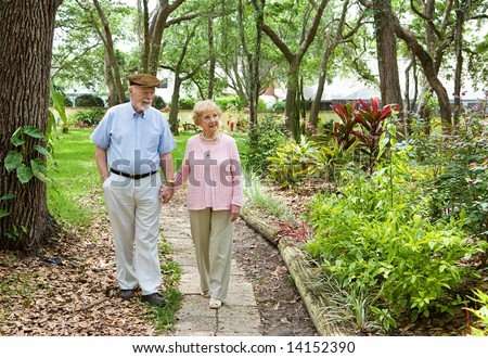 Senior couple walking through the park together. - stock photo