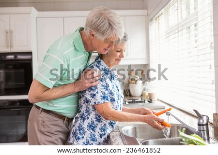 Senior couple washing vegetables at sink at home in the kitchen - stock photo