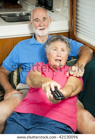 Senior couple watching television in their motor home, shocked by what they are seeing.