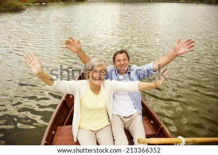 Senior couple waving to the camera on boat on mountain tarn - stock photo