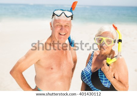 Senior couple wearing snorkel and diving goggles on a sunny day - stock photo