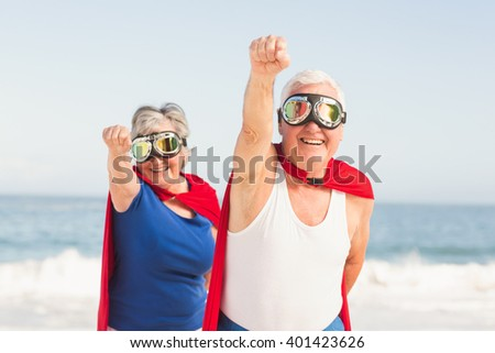 Senior couple wearing superman costume on a sunny day - stock photo
