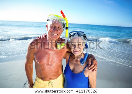 Senior couple with beach equipment at the beach - stock photo