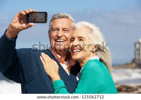 Senior Couple With Camera On Beach - stock photo