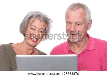Senior couple with computer in front of white background - stock photo