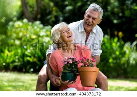 Senior couple with flower pots enjoying in yard - stock photo